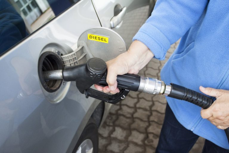 A hand filling up a car with diesel